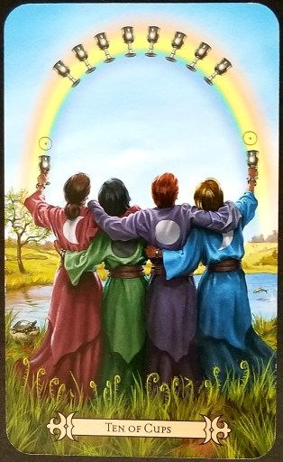 Ten of Cups- Tarot Card: Four people, their backs towards us and arms clasped around each other, stand beneath a rainbow.