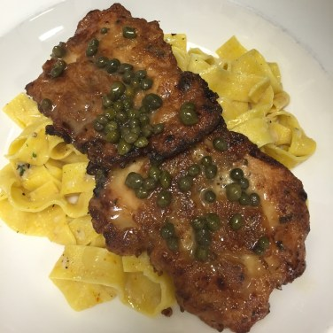 CHICKEN PICCATA - tenderized chicken breast lightly battered then served over saffron pappardelle fresh pasta in a garlic and Asiago sauce