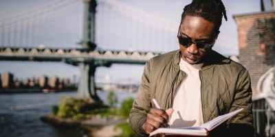 serious african american male with planner on city riverbank