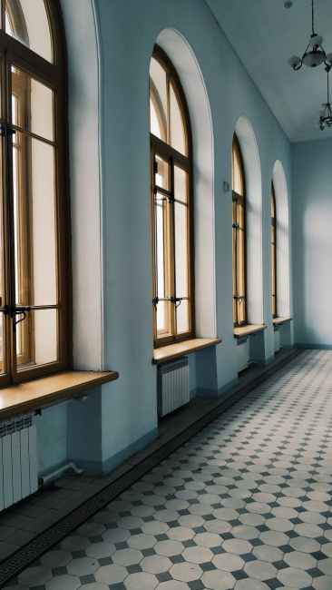 interior of empty light hallway with arched windows