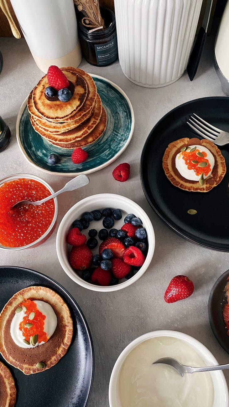 set of appetizing pancakes with berries and caviar served on table