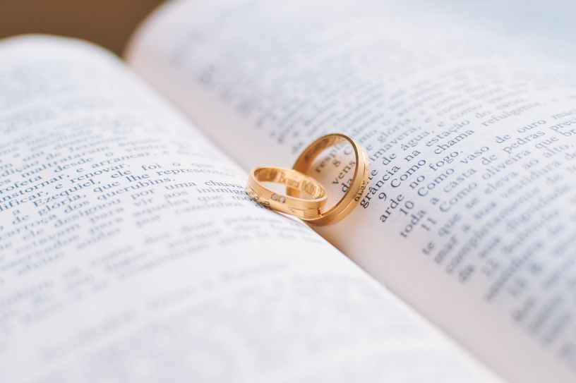 two gold colored wedding bands on book page