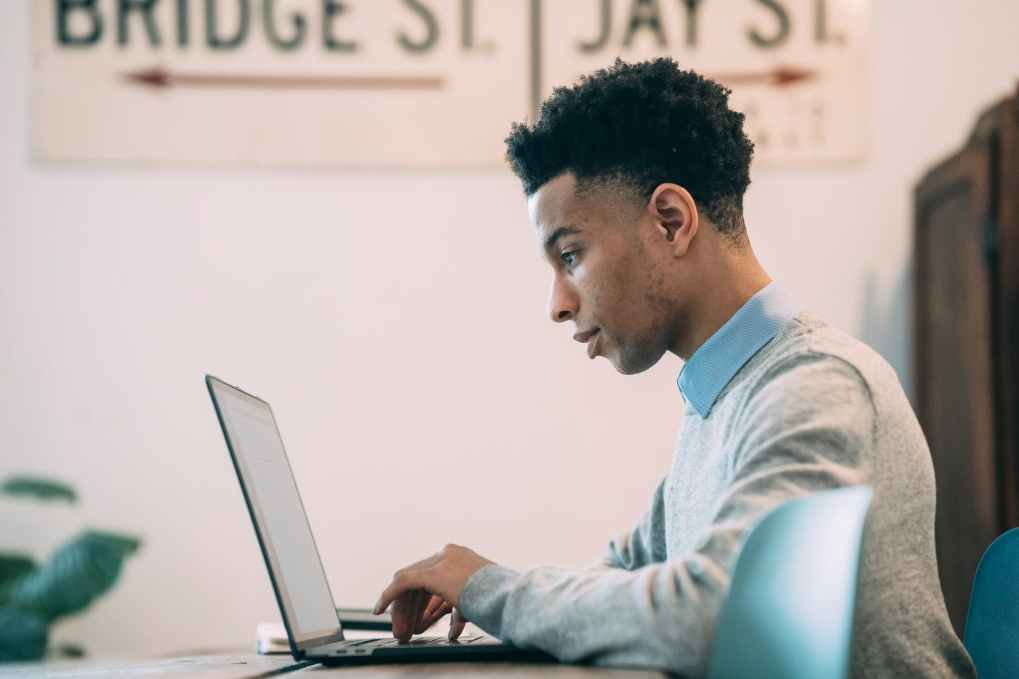 ethnic young freelancer using laptop