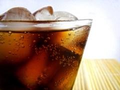 Vaso con bebida de cola y hielo.
