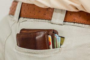Imagen de una cartera que se asoma del bolsillo trasero de un pantalón,  en la que se ven una tarjeta de crédito y varios billetes.
