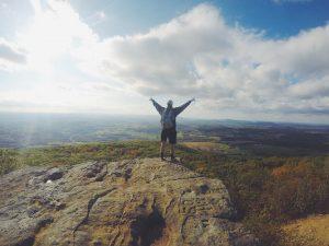 Un hombre en la cima de una montaña con los brazos abiertos y una panorámica de las tierras bajas, las nubes y el cielo.