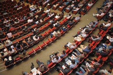 Auditorio grande para conferencias vista desde arriba, en la que ya se encuentran algún asistentes.