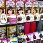 Estantería en una tienda donde se muestran tintes para pelo de diversos colores, de marcas asiáticas.