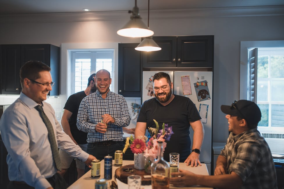 grooms and his friends laughing in a kitchen