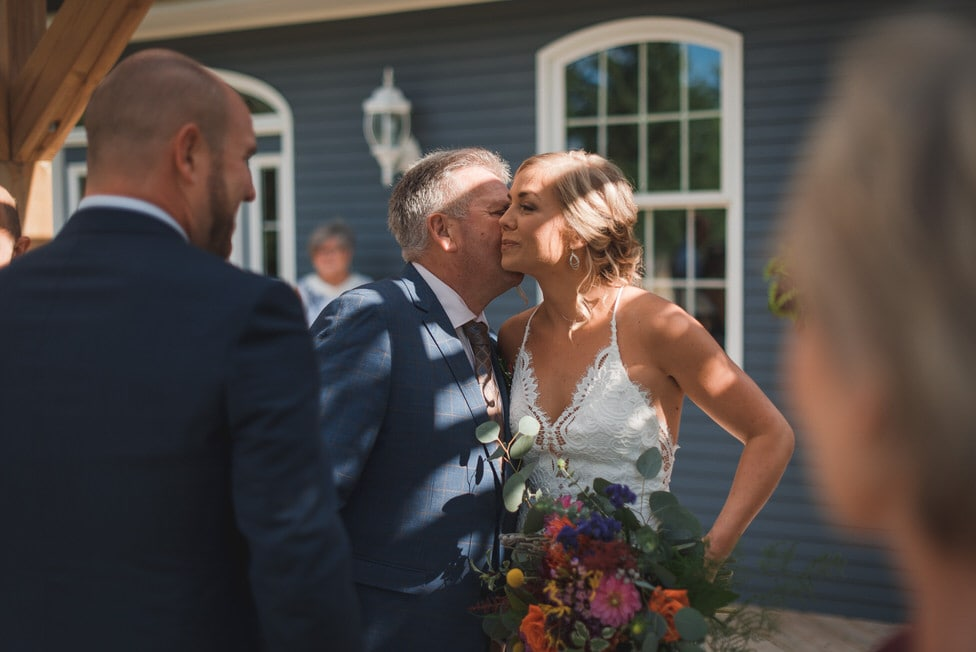 father of the bride kisses bride in emotional moment during backyard wedding ceremony