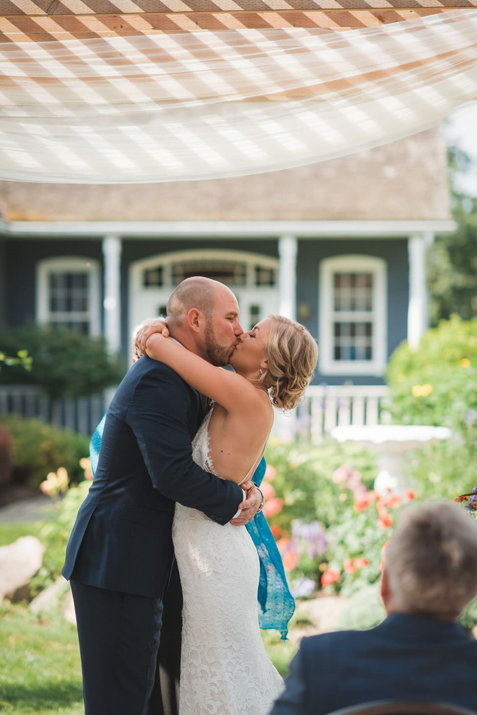 first kiss during backyard wedding ceremony