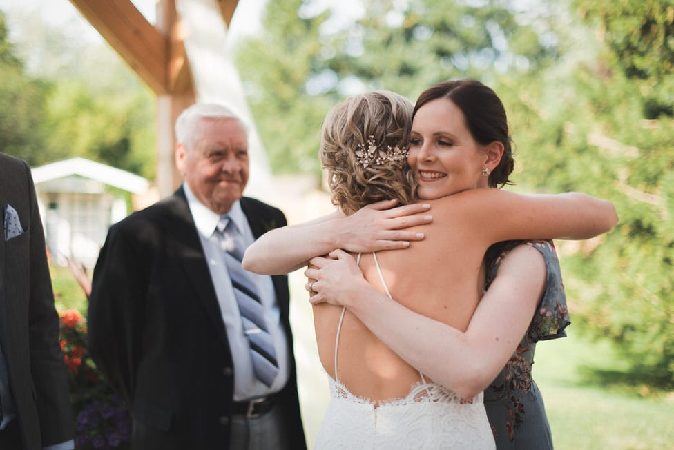 bride hugs a family member in celebration