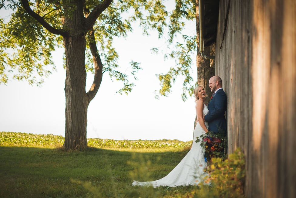 bride and groom lean against wooden barn wall