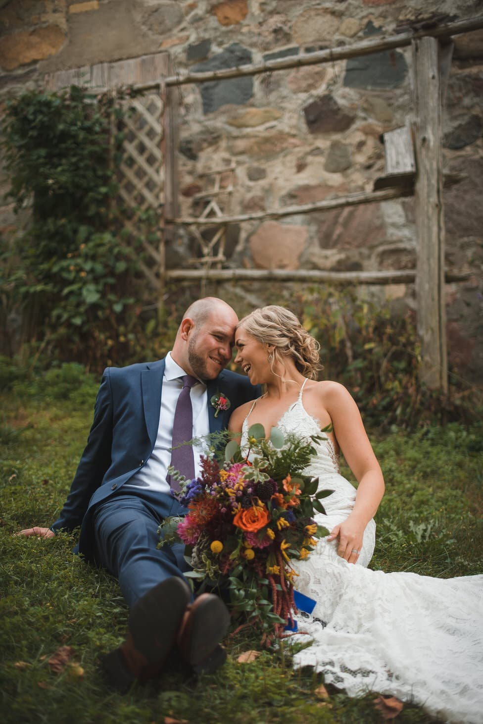 bride and groom sit in grass by stone shed, bouquet by designs by cate stratford