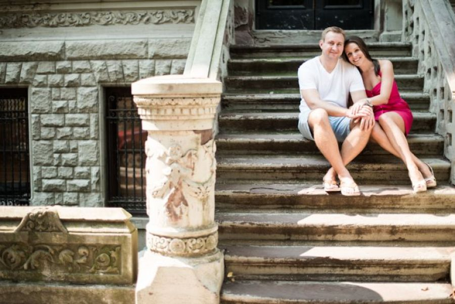 Kathleen and Tim sit on a stoop during their engagement session in New York City. Captured by Ben Lau Photography.