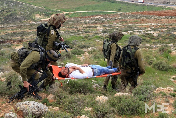 Israeli soldiers carry away an unconscious Palestinian, after refusing to let him get medical treatment CREDIT: Middle East Eye/Ahmad Al-Bazz