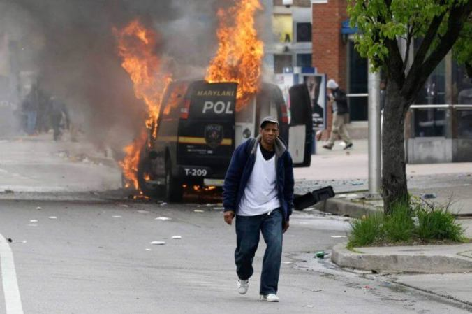 A man walks past a burning police vehicle, Monday, April 27, 2015, during unrest following the funeral of Freddie Gray in Baltimore. Gray died from spinal injuries about a week after he was arrested and transported in a Baltimore Police Department van. (AP Photo/Patrick Semansky)