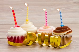 four birthday cupcakes with burning candles on wooden table