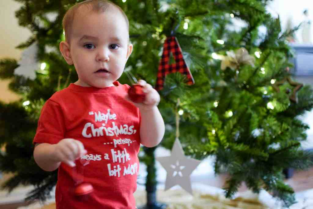 toddler with jingle bell ornaments