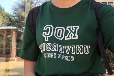 Görselde telefonla üzerimdeki tişörtü çekmişim. ÜZerimde koyu yeşil bir tişört var, tişörtün üzerinde beyaz renkte KOC UNIVERSITY SINCE 1993 yazıyor. arkada iki tane çam ağacı var.