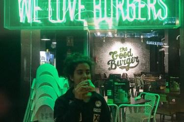 Bir burgercideyim, arkamda cam kapının üstünde we love burger yazıyor yeşil led ışıklarla. Ben de önünde elimde burger yiyorum, üstümde siyah bir kazak, saçlarım toplu, ve sağa bakıyorum.