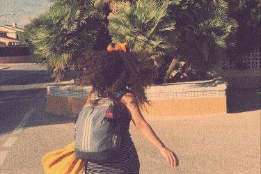 Fotoğrafta arkam dönük şekilde ben varım. Bir yolda yürüyorum, Saçlarım açık ve biraz savrulmuş, sırt çantam var gri, ve çantama takılı sarı şalım var. Üstümde siyah beyaz çizgili bir elbise var kısa. Yolun kenarında ağaçlar görünüyor.