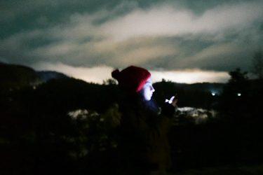 karanlık gece yarısı çekilmiş bir fotoğraf. karanlığın ortasında görünen tek şey ben ve elimdeki telefonun ışığı, ışık yüzüme vurduğu için suratım da parlamış. .arkada biraz beyaz bulut görünüyor, karanlık gökyüzünden hafif sıyrılmışlar şehirden yansıyan ışıkla.