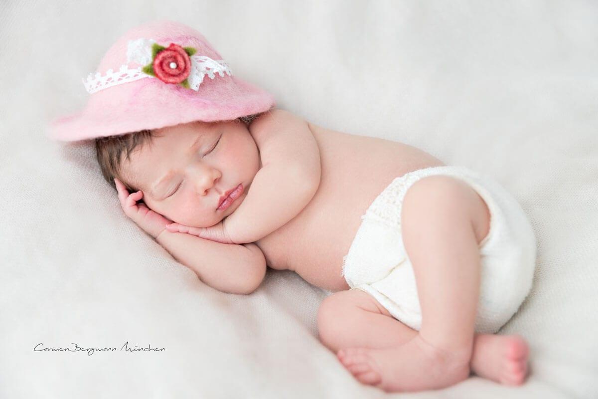 Neugeborenes Shooting mit Hut auf Decke romantisch