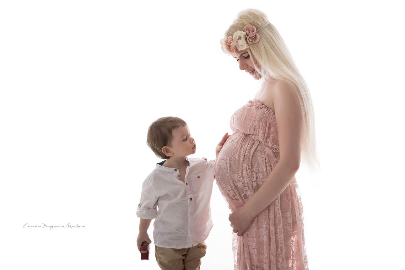 Schwangere Frau mit Babybauch und Kind in Fotostudio mit Kleid und Blumen