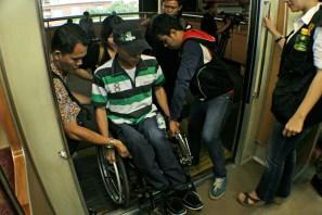 Pengguna kursi roda menyebrangi Barrier Gap jembatan pintu gerbong penumpang. ( Tajuk.co / Aljon Ali Sagara )