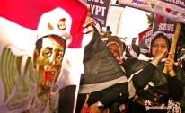 Seorang demonstran memandang spanduk ilustrasi kekejian militer Mesir. (Aljon Ali Sagara / BeritaKedaulatan.com)