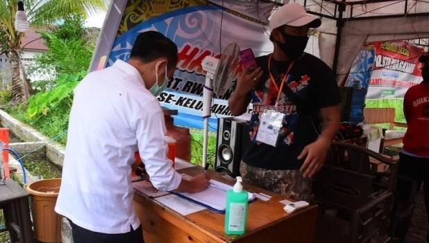 Anggota pos penjagaan Jalan Menteng XII Kota Palangka Raya saat mengecek suhu tubuh kepada warga yang ingin memasuki wilayah Jalan Menteng XII, Jum'at (28/5).