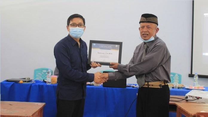 Drs. H. Ahmad Sujai M.Pd., Pembina Yayasan Assalam saat memberikan piagam kepada Hendriwanto, S.Pd., M.Pd. (Dok. Istimewa)