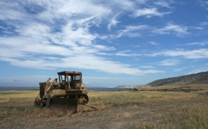 An abandoned tractor on Santa Rosa Island, indicative of 20th-century human exploitation of the Channel Islands. Santa Cruz Island can be seen in the distance on the left. (Levi Gadye)
