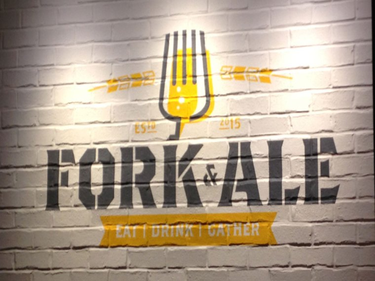 "A white brick wall painted with a yellow fork and the words ""Fork & Ale"""