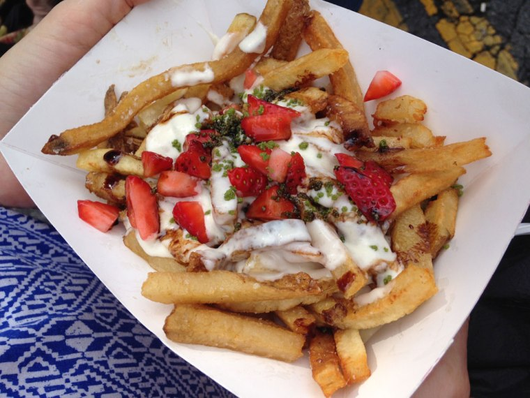 Photo of a paper boat filled with French fries topped with creamy cheese, strawberries and herbs.