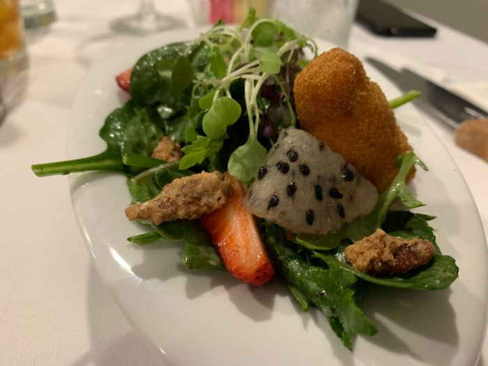 Strawberry salad with dragon fruit, candied pecans and a goat cheese croquette