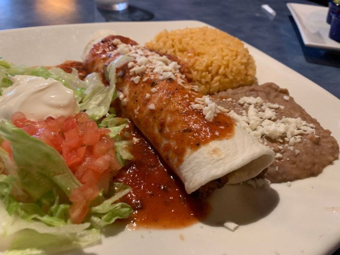 The Burrito Alebrije was stuffed with ground beef and topped with tomato sauce and cheese, and served with rice, refried beans, and lettuce with sour cream.