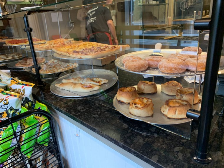 Pizzas, pepperoni bites, and sweets behind the counter at Oliviero's in Douglassville