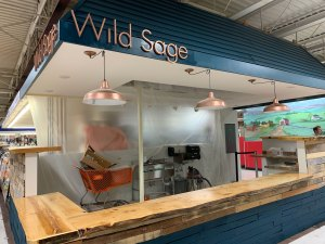 The Wild Sage stand at Fairgrounds Farmers Market features a blue overhang and wooden counters for a modern-rustic contrast