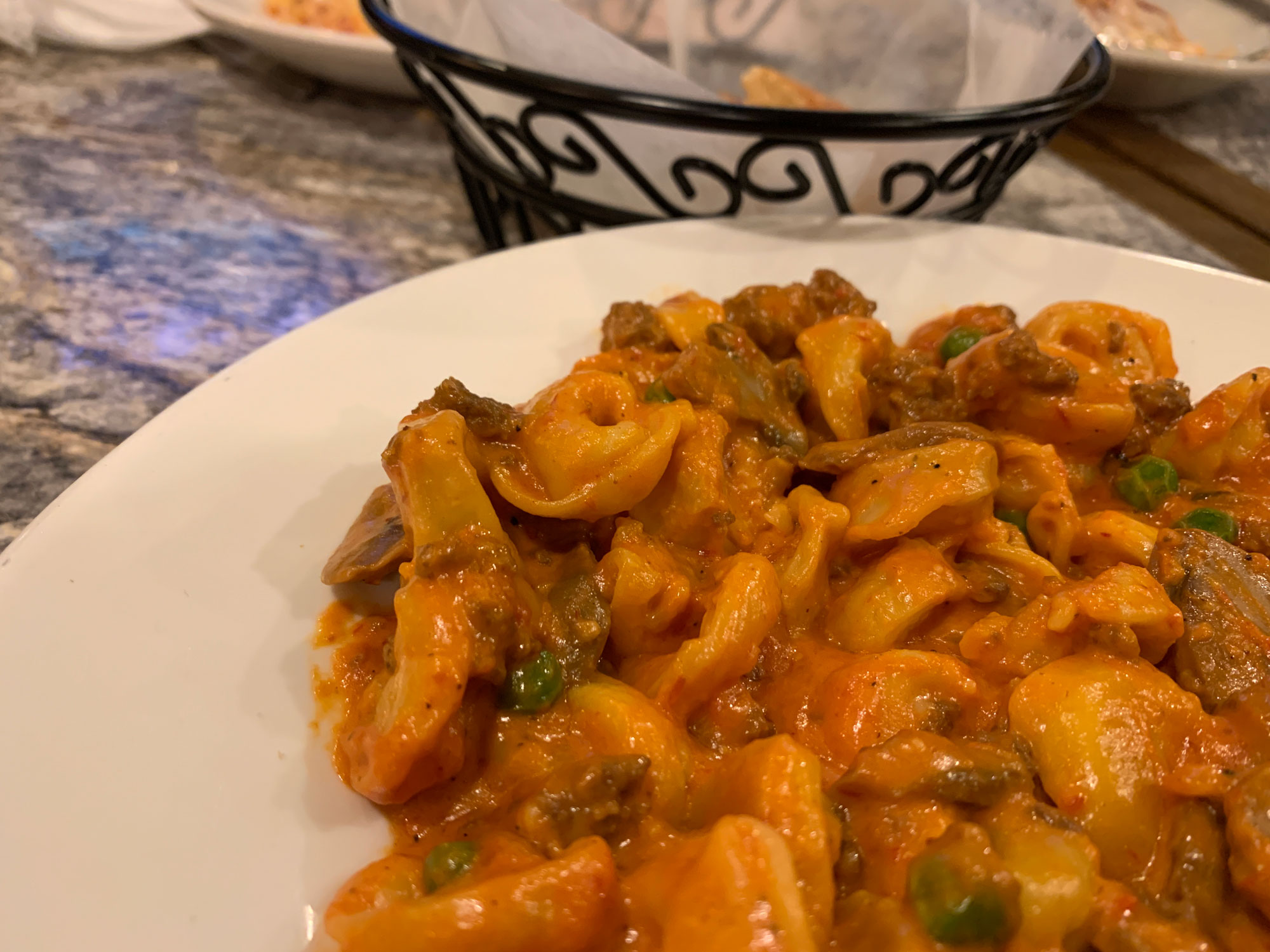 A plate of tortellini topped with meat sauce, peas and mushrooms from Gino's Cafe in Shillington