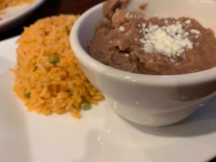 A bowl of refried beans with yellow rice on a plate from Norte Sur