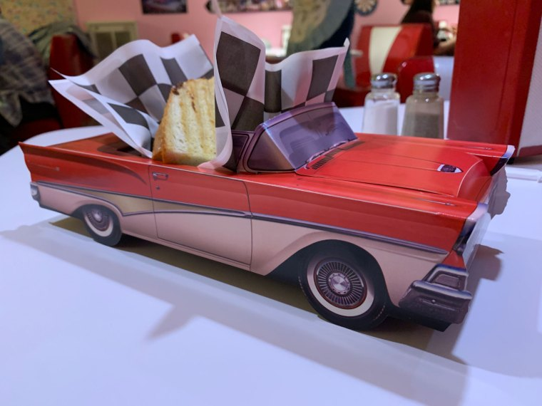A kids meal featuring Half a grilled cheese sandwich served in a 3D cardboard paper Ford Fairlane classic car