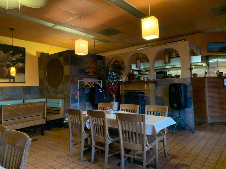 A view of one of the dining areas at Aladdin Mediterranean Restaurant with a table for four in the foreground and a fireplace in the background