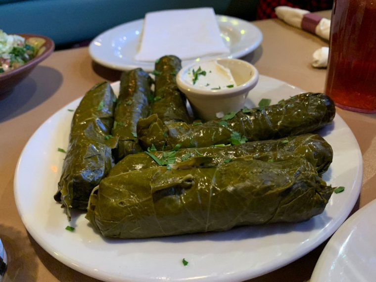 A plate with six rolled and stuffed grape leaves and a side of yogurt for dipping from Aladdin Mediterranean Restaurant
