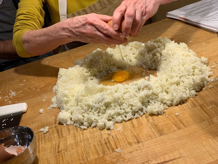 Eggs are dropped into the center of the flour and potato mixture