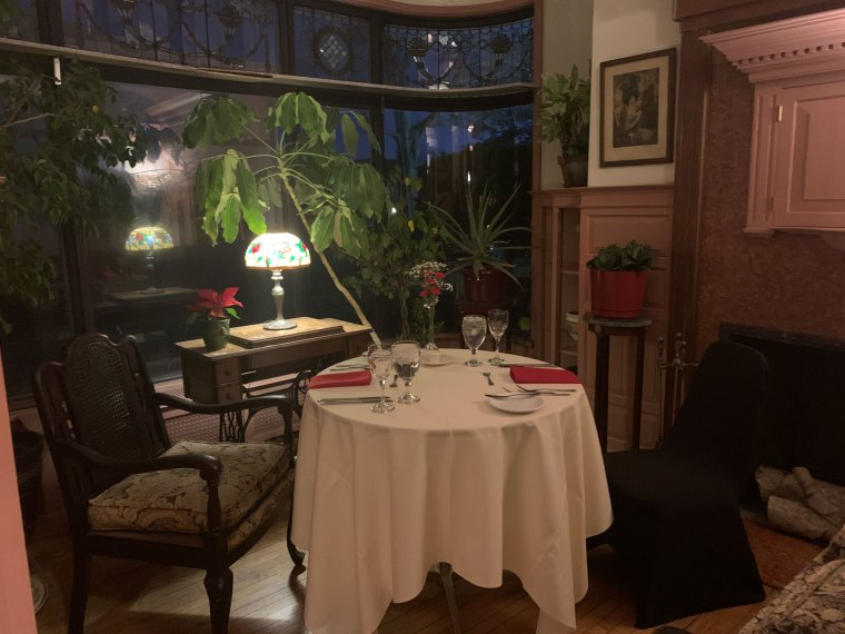 A table for two is set up in a corner room with large picture window and greenery at the Inn at Centre Park