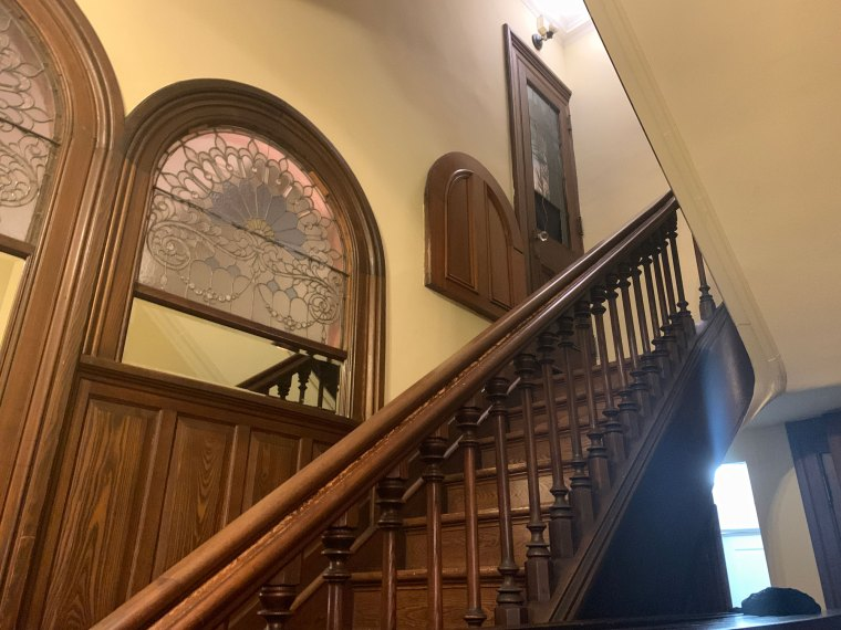 A wooden staircase in front of art glass windows at the Inn at Centre Park