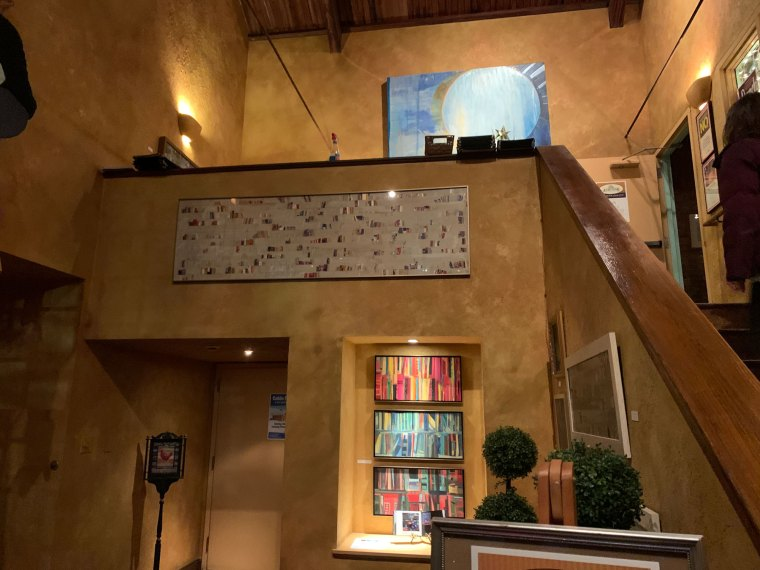 The entryway at Judy's on Cherry includes a staircase lined with paintings and sculptures from local artists