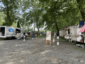 Wide shot of food trucks in a picnic grove